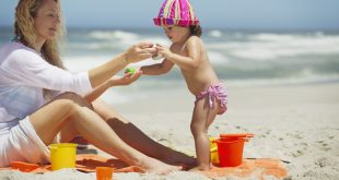 Woman and her daughter playing with pail and shovel on the beach